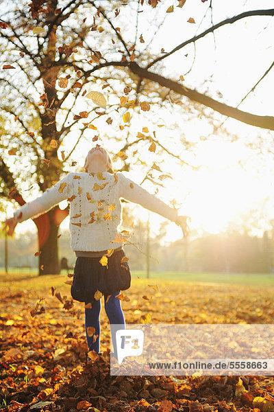 Lächelndes Mädchen spielt im Herbstlaub
