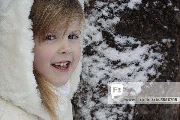 Lächelndes Mädchen steht draußen im Schnee