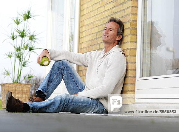 Mann isst Apfel auf der Veranda