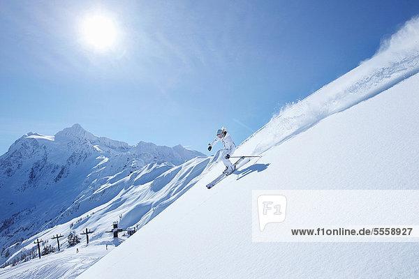 Skifahrer beim Abfahren der verschneiten Piste