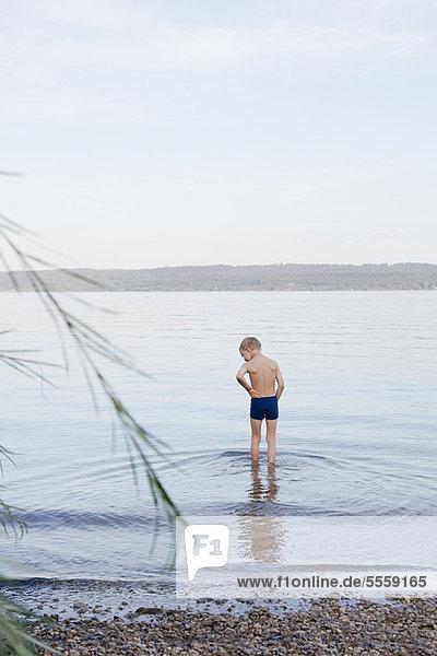 Junge waten am felsigen Strand
