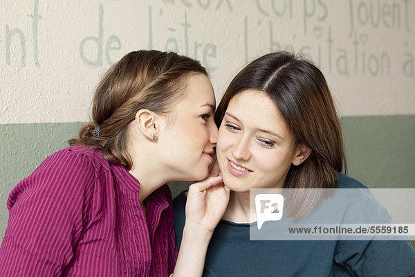Frauen flüstern sich zu.