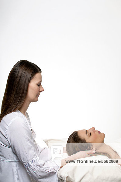 A young woman performing a Reiki treatment on a patient