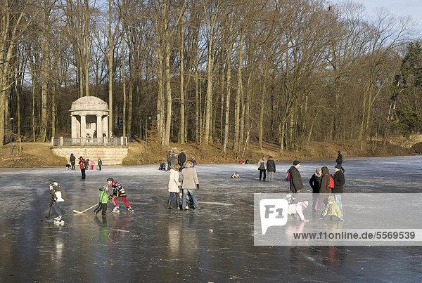 Menschen auf einem zugefrorenen See im Stadtwald  Krefeld  Nordrhein-Westfalen  Deutschland  Europa