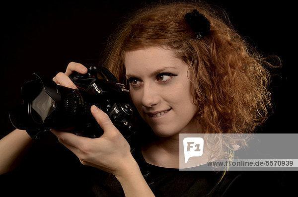 Rothaarige Frau beim Fotografieren mit einer Kamera