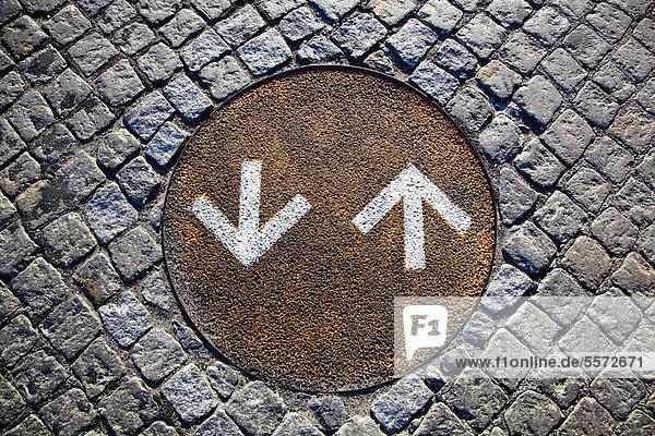 Richtungspfeile für Radfahrer auf einem verrosteten Kanaldeckel auf dem Boden im Stadtteil Belem in Lissabon  Portugal  Europa