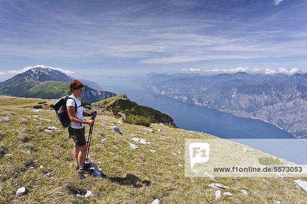 Bergsteiger auf dem Monte Altissimo oberhalb von Nago  unten der Gardasee  hinten der Monte Baldo  Trentino  Italien  Europa
