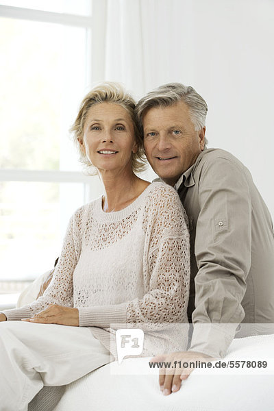 Erwachsenes Paar auf dem Bett sitzend  Porträt