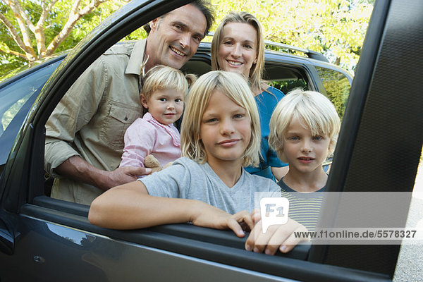 Familie posiert neben dem Auto  Blick durch offenes Fenster  Porträt