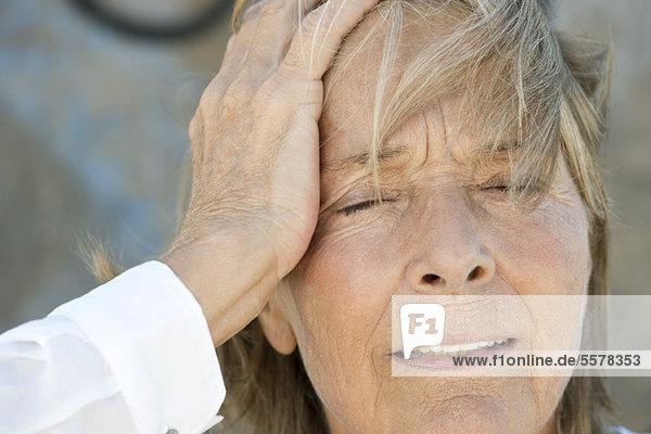 Seniorin hält Kopf  Augen geschlossen