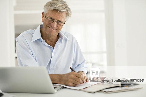 Älterer Mann  der zu Hause arbeitet