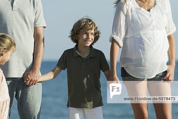Ein Junge am Strand mit seiner Familie  der die Hände seiner Eltern hält.