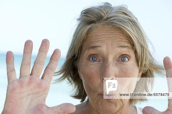 Seniorin mit erhobenen Händen in Stoppgeste