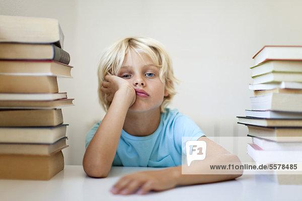 Junge sitzt zwischen zwei Stapeln von Büchern mit gelangweiltem Gesichtsausdruck.