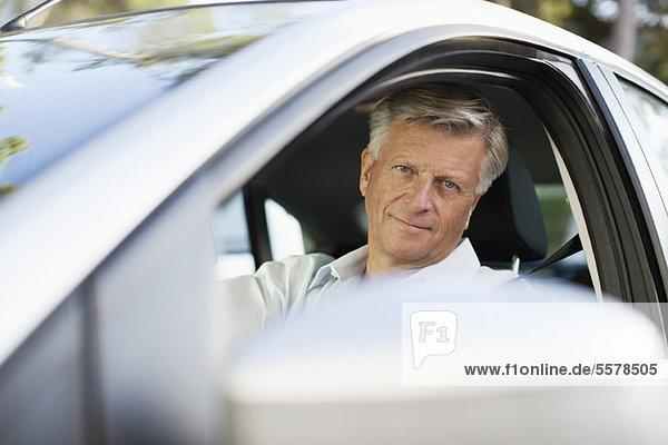 Mann fährt Auto  schaut aus dem Fenster auf die Kamera.