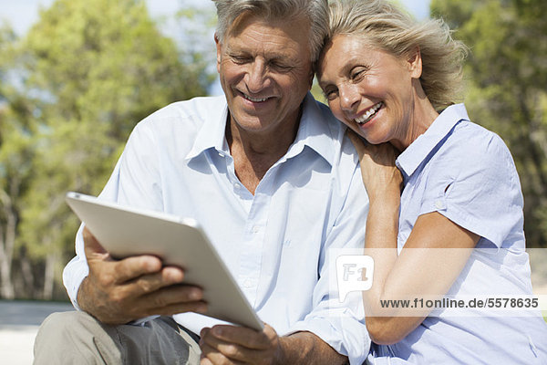 Reife Paare mit digitalem Tablett im Freien