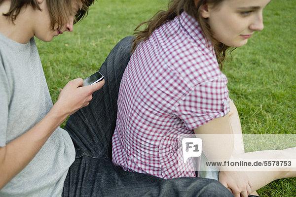 Junges Paar sitzt zusammen auf Gras  Mann Textnachricht