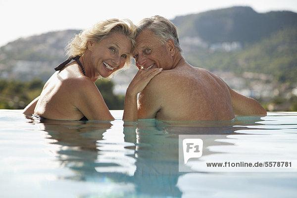 Reife Paare entspannen sich gemeinsam im Pool
