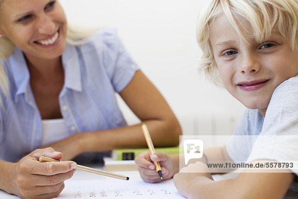 Junge macht Hausaufgaben  lächelt in die Kamera.