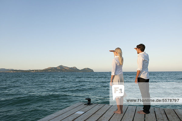 Paar auf dem Pier stehend mit Blick auf die Seitenansicht