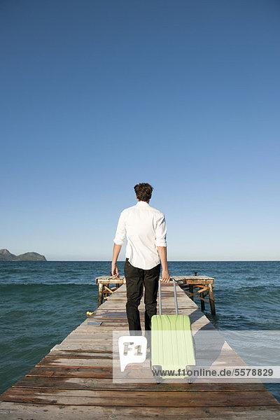 Mann  der das Gepäck zum Ende des Piers zieht  Rückansicht