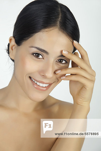 Woman touching face  looking through fingers at camera