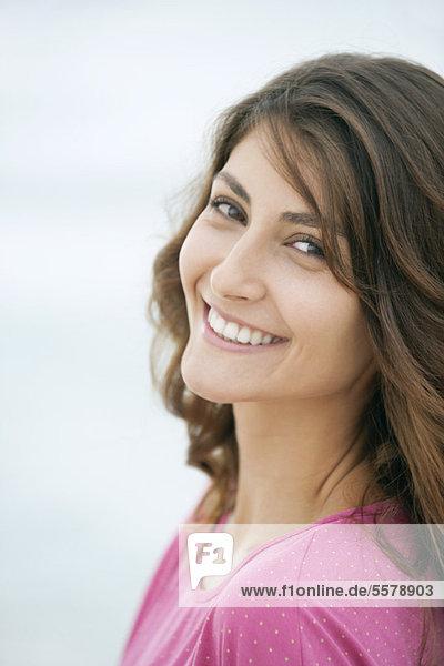 Junge Frau lächelt über die Schulter  Portrait