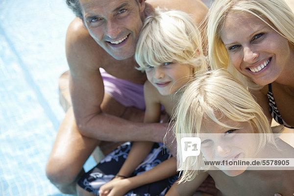 Familie sitzt zusammen neben dem Schwimmbad  Porträt