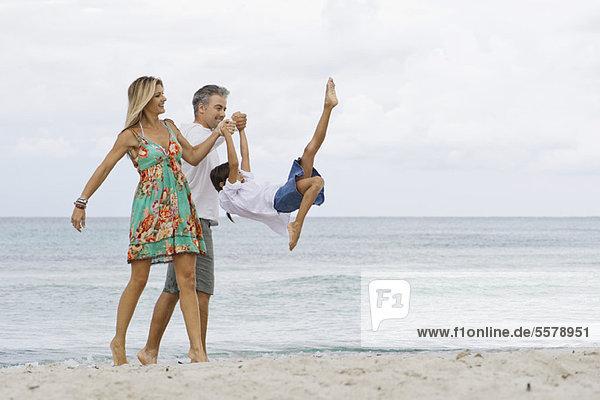 Eltern schwingende Tochter beim Spaziergang am Strand