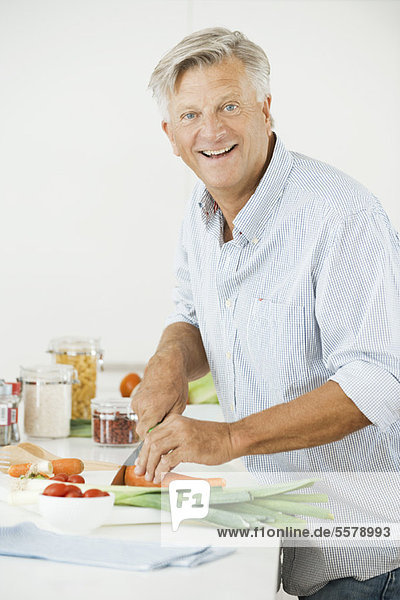 Älterer Mann  der Gemüse hackt  lächelt in die Kamera.