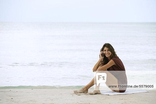 Junge Frau am Strand sitzend  mit Handy