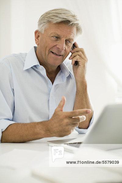 Mann  der auf dem Handy spricht  während er den Laptop benutzt.