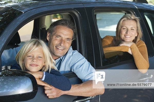Familie zusammen im Auto  aus den Fenstern lehnend und lächelnd vor der Kamera