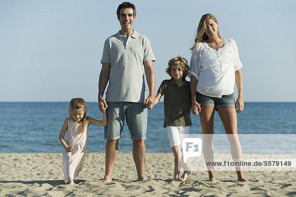 Familie hält sich am Strand an den Händen