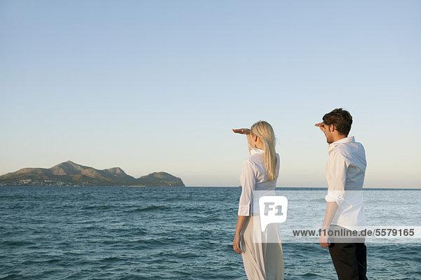 Paar steht am Wasser und schaut auf die Aussicht.