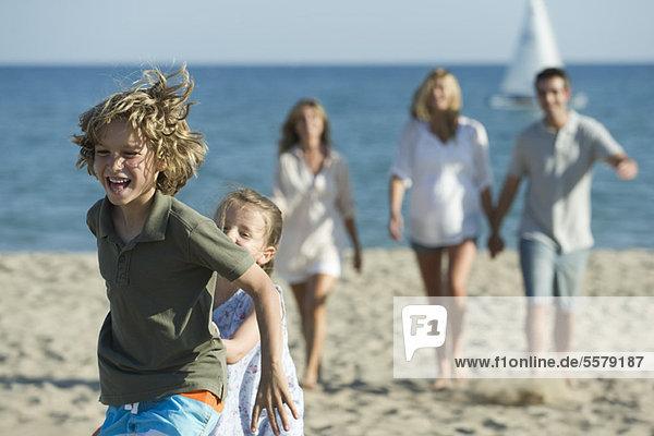Junge Geschwister spielen am Strand  Familie im Hintergrund