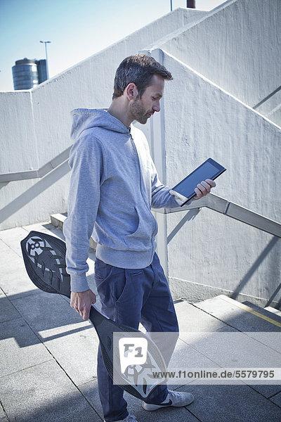 Mann mit Ipad und Waveboard im Freien