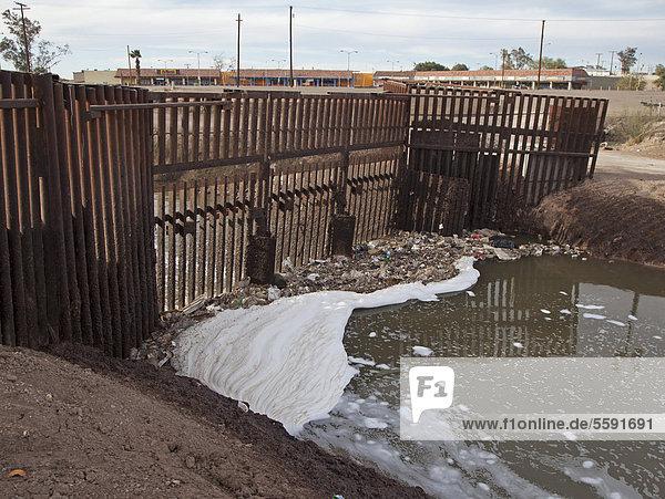 Der stark verschmutzte New River  wie er die USA von Mexiko her erreicht  die Umweltverschmutzung resultiert aus einer Mischung von ungeklärtem Abwasser  landwirtschaftlichen Abflüssen und Gewerbemüll  die Barriere im Fluss verhindert  dass Migranten die USA über den Fluss erreichen  um illegal in die USA einzureisen Calexico  Kalifornien  USA