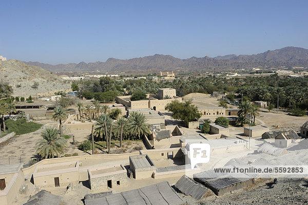 Gesamtansicht der Oase und Enklave Hatta mit Moschee und Dattelpalmen und das Hadschar-Gebirge am Horizont  Vereinigte Arabische Emirate  Arabische Halbinsel  Naher Osten
