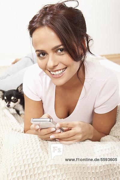 Junge Frau am Telefon mit Chihuahua  lächelnd  Porträt