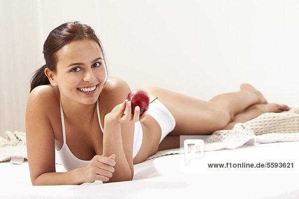 Junge Frau mit Apfel  lächelnd  Portrait