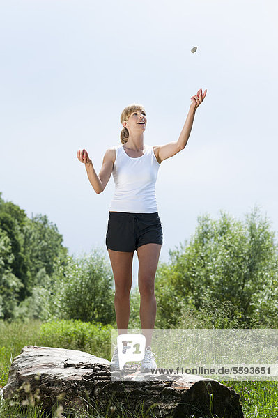 Mid adult woman juggling with stone on tree log  smiling