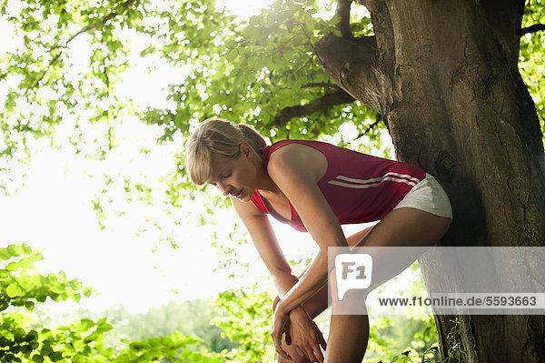 Mittlere erwachsene Frau entspannt sich auf einem Baum