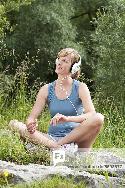 Mittlere erwachsene Frau  die Musik hört  lächelnd
