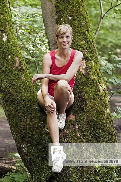 Mittlere erwachsene Frau auf Baum ruhend  lächelnd  Portrait