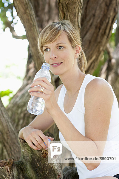Mid adult woman with water bottle  smiling
