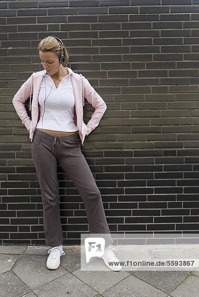 Deutschland  Nordrhein-Westfalen  Düsseldorf  Junge Frau beim Musikhören auf der Straße