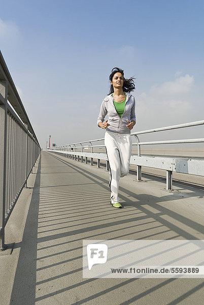 Deutschland  Nordrhein-Westfalen  Düsseldorf  Junge Frau läuft auf Brücke