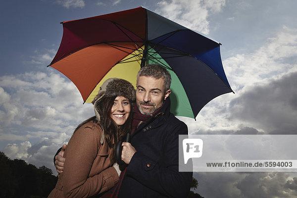 Deutschland  Köln  Paar mit Schirm  lächelnd  Portrait