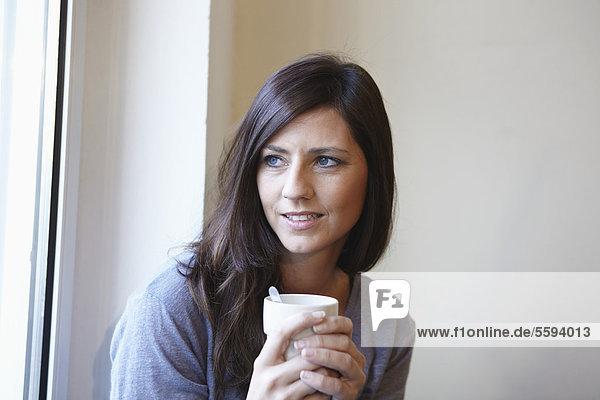 Mittlere erwachsene Frau am Fenster mit Kaffee  lächelnd